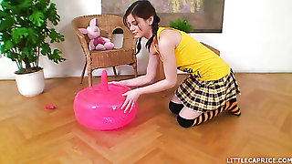 Attractive and hot brunette teen babe in arms strips and rides a yoga ball